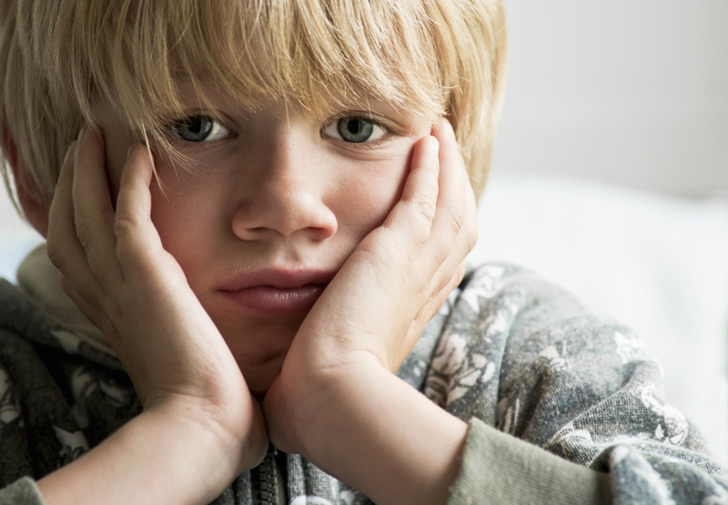 Sad, young boy sits with his face in his hands.