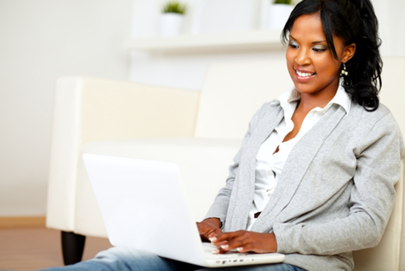 Woman smiles while working on laptop while sitting on couch.