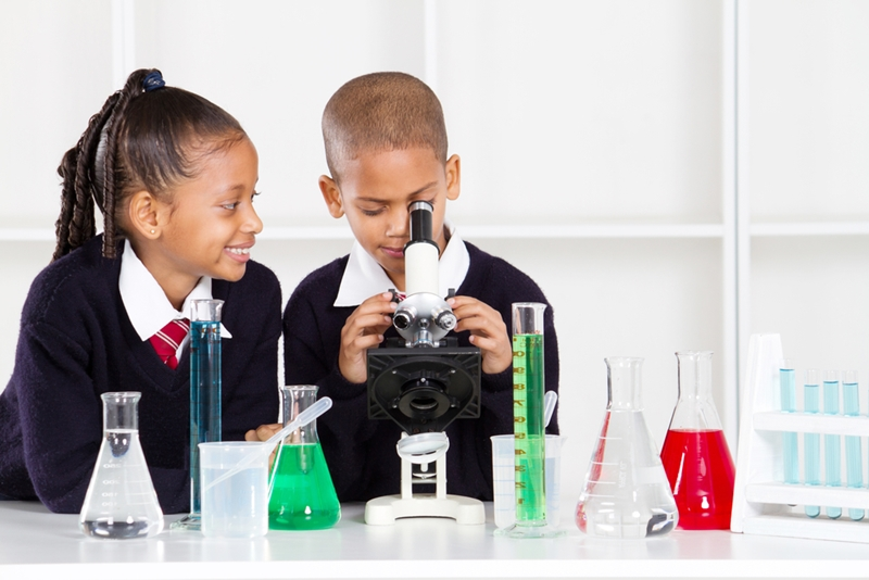 Two young students look at a microscope surrounded by beakers and test tubes.